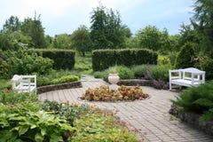 Jardín con dos bancos blancos Imagen de archivo