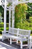 Jardín con el banco blanco Fotografía de archivo