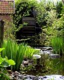 Jardín con la rueda de molino de agua Fotos de archivo libres de regalías