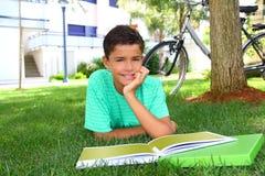 Jardín de colocación adolescente de la hierba verde del muchacho que estudia Fotografía de archivo libre de regalías