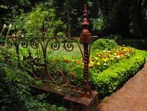 Jardín de flores con la puerta antigua del hierro labrado Imagen de archivo