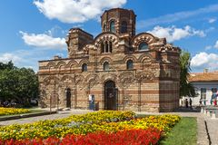 Jardín de flores delante de la iglesia antigua de Cristo Pantocrator en la ciudad de Nessebar, Burg imagen de archivo