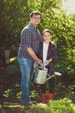 Jardín de riego sonriente del padre con la pequeña hija Foto de archivo
