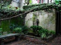 Jardín del patio con los ladrillos, el banco de piedra, y las vides Foto de archivo libre de regalías