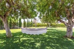 Jardín del verano con la hamaca de la ejecución para la relajación Foto de archivo libre de regalías