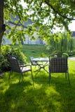 Jardín hermoso con la tabla y la silla blancas imagenes de archivo