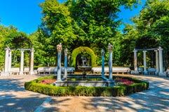 Jardín hermoso rodeado por los árboles, los arcos y las columnas foto de archivo libre de regalías