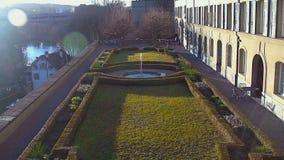 Jardín iluminado por el sol hermoso con la fuente agradable cerca de la mansión costosa, vida de lujo almacen de video