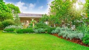 Jardín inglés de la cabaña en el patio trasero en una casa, paisaje infomal del césped de la hierba verde adornar con las hoj imagenes de archivo