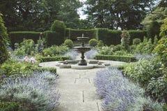 Jardín inglés formal con las camas de la fuente y de la lavanda Imágenes de archivo libres de regalías