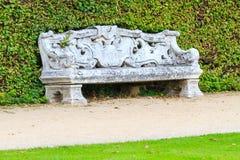 Jardín inglés ornamental con el banco de piedra Fotos de archivo libres de regalías