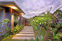 Jardín moderno de la casa con la iluminación colorida debajo del cielo Imagen de archivo