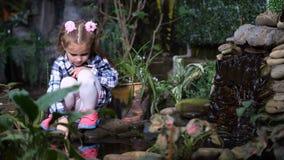 Jardín tropical hermoso Cerca del agua sienta a una niña y toca el agua con su finger 4K MES lento almacen de metraje de vídeo