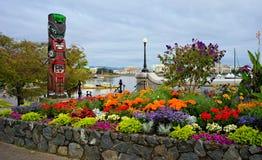 Jardín y tótem en los bancos de Victoria Inner Harbour, Columbia Británica, Canadá imagen de archivo