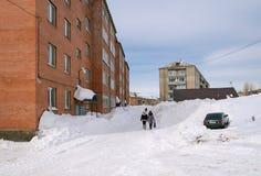 A jarda de uma casa residencial do tijolo, coberta com a neve imagens de stock royalty free