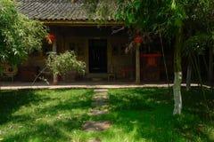 Jarda gramínea antes da casa de madeira telha-telhada antiga na soma ensolarada Imagem de Stock Royalty Free