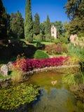 Jardim bonito com lagoa e a igreja pequena Imagens de Stock Royalty Free
