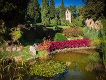 Jardim bonito com lagoa e a igreja pequena Imagens de Stock