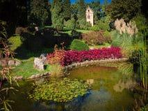 Jardim bonito com lagoa e a igreja pequena Imagem de Stock