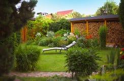 Jardim bonito do verão com madeira do fogo da sala de estar do chaise do coushion Imagem de Stock