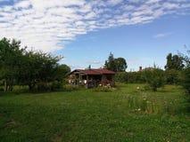 Jardim com a casa de madeira pequena Fotos de Stock Royalty Free
