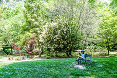 Jardim com a estátua do menino no banco Imagem de Stock Royalty Free