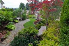 Jardim com os bancos da pedra do trajeto do tijolo e a fonte de água Imagens de Stock Royalty Free