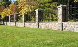 Jardim com parede de pedra Fotos de Stock