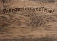 Jardim da cerveja das palavras do alemão aberto na madeira imagens de stock