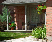 Jardim da frente ajardinado de uma casa com flores e gramado verde Fotografia de Stock