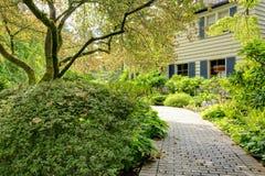 Jardim da frente bonito com passagem e a grande casa marrom cinzenta fotografia de stock royalty free