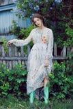 Jardim de Eden Flores em torno da menina no vestido cinzento e em botas verdes Retrato de uma menina atrativa nova no verão ensol Imagens de Stock Royalty Free