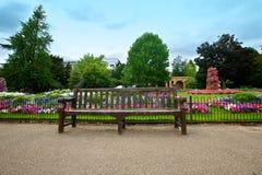 Jardim de flor Manicured com um banco de madeira Fotos de Stock Royalty Free