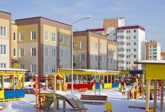 Jardim de infância novo, campo de jogos e edifícios novos. Foto de Stock Royalty Free