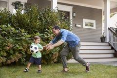 Jardim de Playing Soccer In do pai com filho fotos de stock royalty free