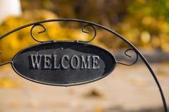Jardim decorativo com o quadro indicador bem-vindo do ferro no fundo da natureza Imagens de Stock Royalty Free
