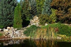 Jardim do outono com lagoa artificial e a cachoeira de pedra secada que refletem na superfície da água Imagens de Stock Royalty Free