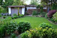 Jardim fresco da mola com as coníferas e as árvores dos arbustos dos perennials imagem de stock