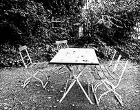 Jardim outonal, cadeiras, tabela e folhas caídas Imagem de Stock Royalty Free