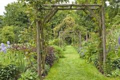 Jardim verde do verão com a passagem sob o arco da flor Foto de Stock Royalty Free