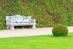 Jardin anglais ornemental avec le banc en pierre Photographie stock libre de droits