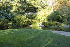 Jardin avec la pelouse et l'étang agréables Photographie stock libre de droits