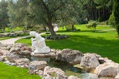 Jardin avec la rivière et les statues Images stock
