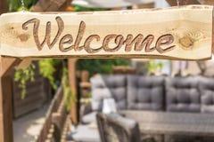 Jardin confortable avec le coin salon moderne dans la conception de rotin et le signe bienvenu en bois photo libre de droits
