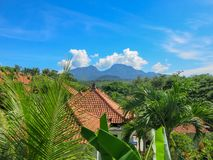 Jardin d'agrément tropical avec la grande piscine R?flexion sur la surface de l'eau À l'arrière-plan les montagnes de Lempuyang image libre de droits