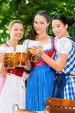 Jardin de bière - amis dans des vêtements traditionnels en Bavière Images stock