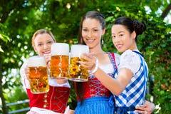 Jardin de bière - amis dans des vêtements traditionnels en Bavière Photographie stock