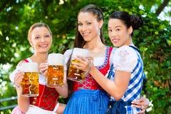 Jardin de bière - amis dans des vêtements traditionnels en Bavière Photos stock