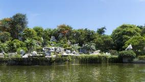 Jardin de roche avec l'étang et les arbres Photographie stock