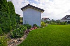 Jardin en bois blanc jeté ou hutte avec des fleurs et des plantes images stock